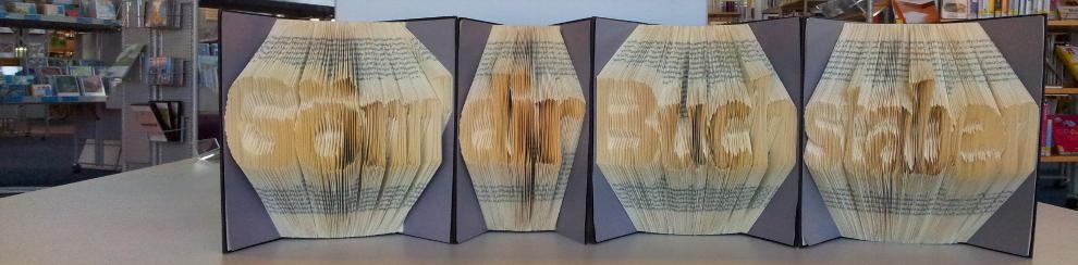 4 Bücher mit dem gefalteten Schriftzug